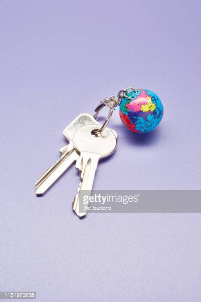 High angle view of keyring with a small globe on colored background