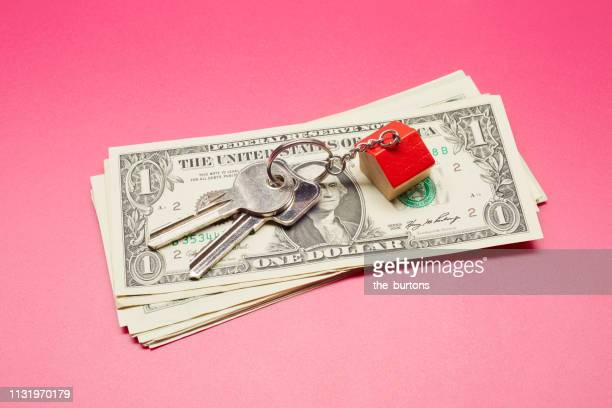 High angle view of keyring with a small house and American Dollar banknotes on colored background