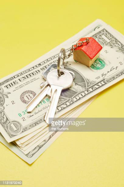 High angle view of keyring with a small house and Dollar banknotes on colored background