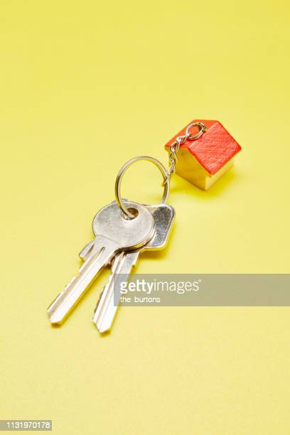 High angle view of keyring with a small house on colored background
