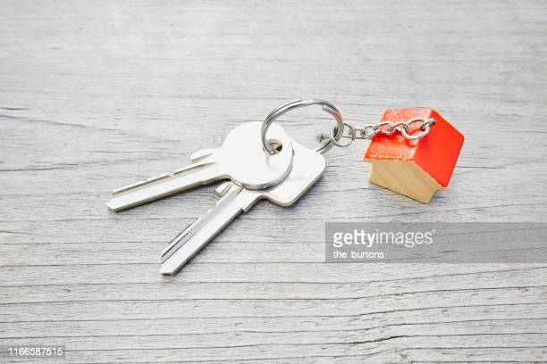 high angle view of keyring with a small red house and keys on wooden background - キーホルダー ストックフォトと画像