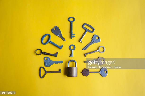 high angle view of keys and padlock on yellow background - padlock stock photos and pictures