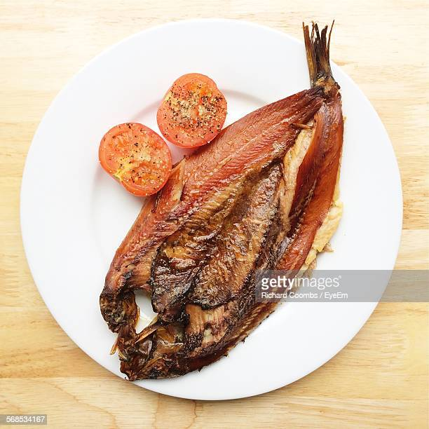 High Angle View Of Kipper By Tomatoes Served In Plate On Table