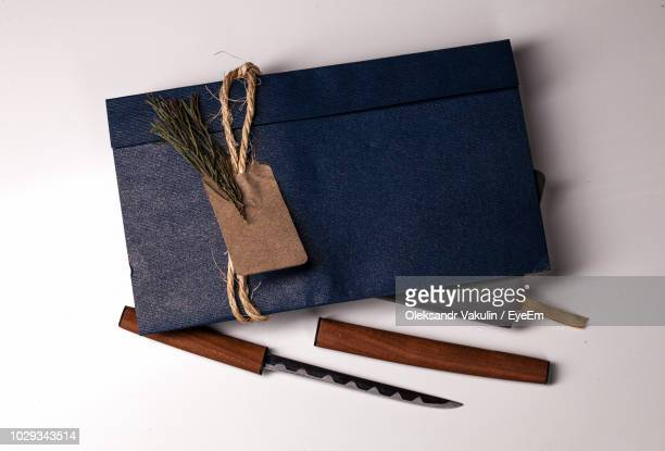 High Angle View Of Knife By Envelope On Diary Against White Background