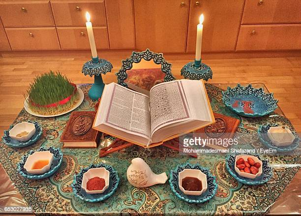 high angle view of koran amidst foods and lit candles on rug during nowruz - persian new year stock photos and pictures