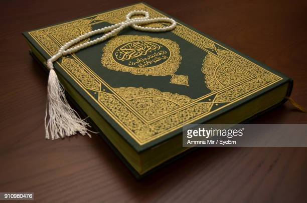 High Angle View Of Koran On Wooden Table