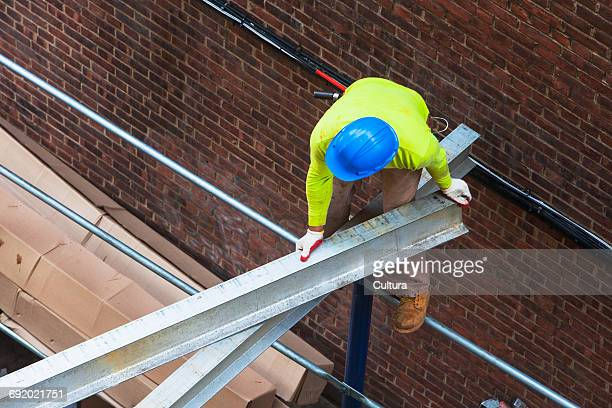 High angle view of labourer moving girder at construction site