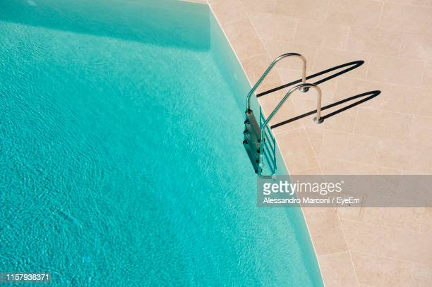high angle view of ladder on swimming pool - piscine photos et images de collection