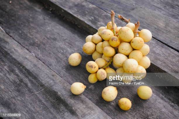 high angle view of lansium domesticum fruits on wooden table - frische stockfoto's en -beelden