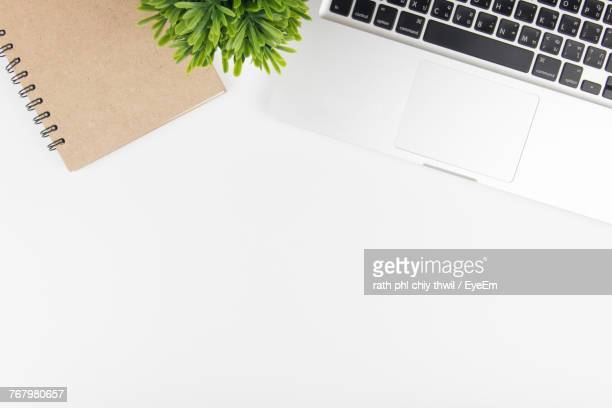 high angle view of laptop and diary on white desk - office desk top view stock photos and pictures