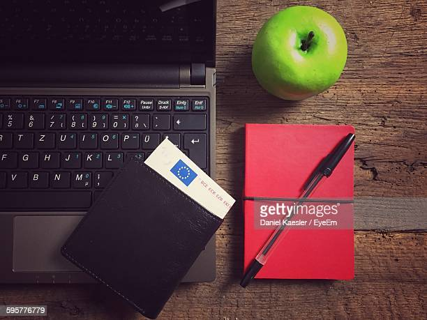 High Angle View Of Laptop And Notepad With Green Apple On Table