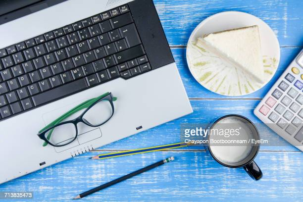 High Angle View Of Laptop By Sandwich And Milk With Calculator On Wooden Table