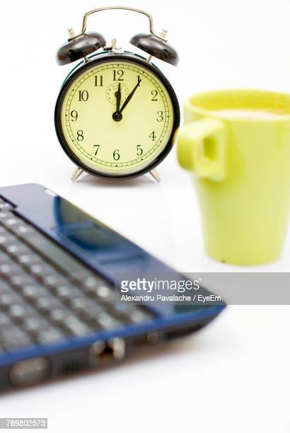 High Angle View Of Laptop With Clock And Drink On White Background