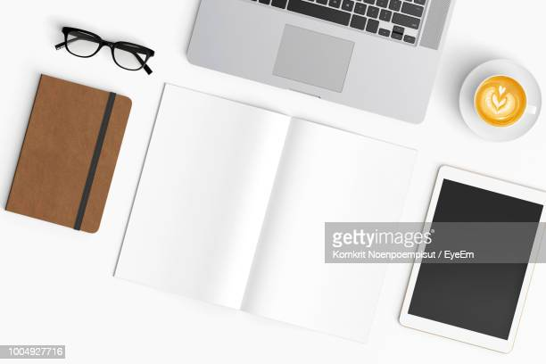 High Angle View Of Laptop With Coffee Cup And Open Book On Table