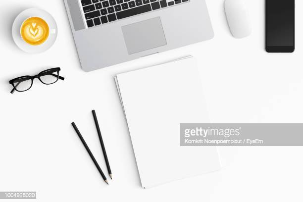High Angle View Of Laptop With Coffee Cup And Papers On Table