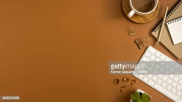 high angle view of laptop with drink and office supplies on brown background - saucer stock pictures, royalty-free photos & images