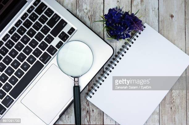 High Angle View Of Laptop With Magnifying Glass And Book On Table