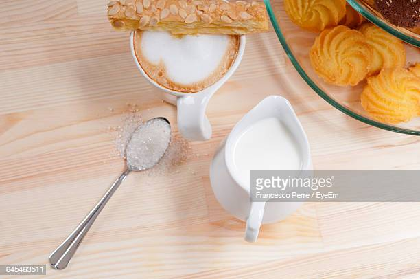 High Angle View Of Latte And Creamer On Table