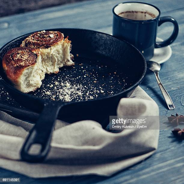High Angle View Of Leftover Tart In Pan By Coffee Cup On Table