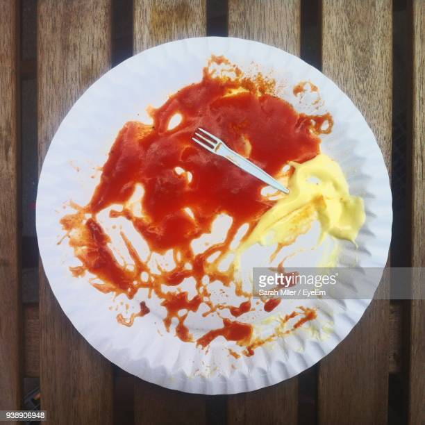 high angle view of leftovers in plate on table - paper plate stock photos and pictures
