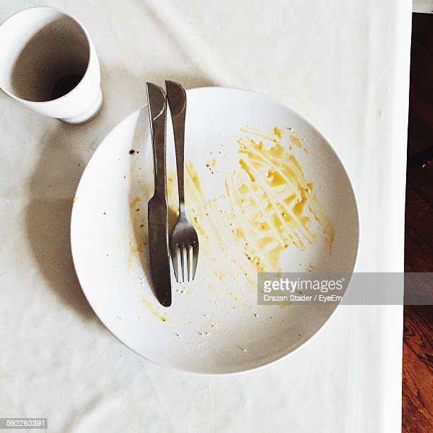 high angle view of leftovers plate with fork on table - finishing stock pictures, royalty-free photos & images