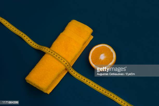 high angle view of lemon tape measure on yellow towel over blue background - magersucht stock-fotos und bilder