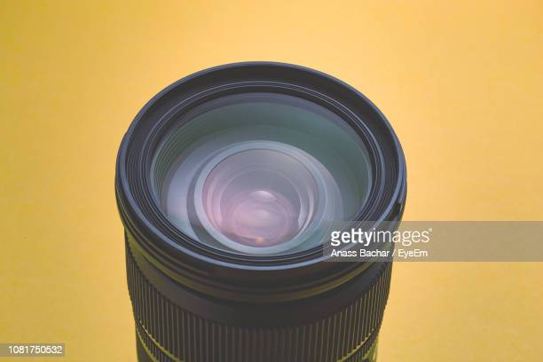 High Angle View Of Lens Against Yellow Background
