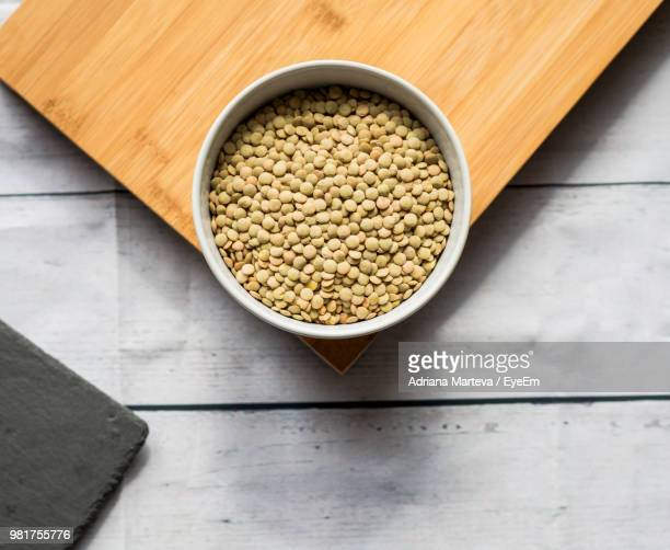 high angle view of lentils in bowl on table - lentil stock pictures, royalty-free photos & images