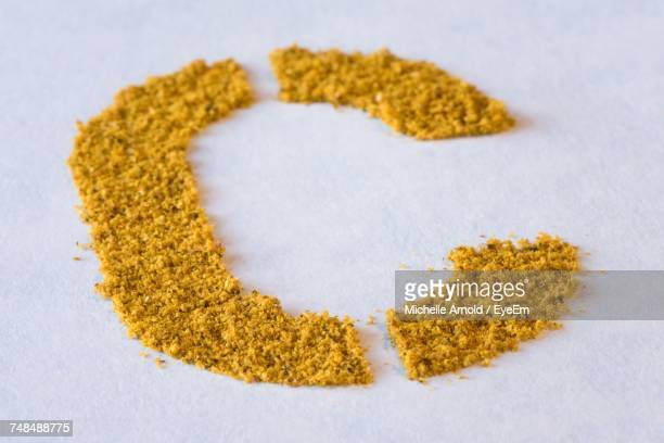 High Angle View Of Letter C Made From Curry Powder On White Table