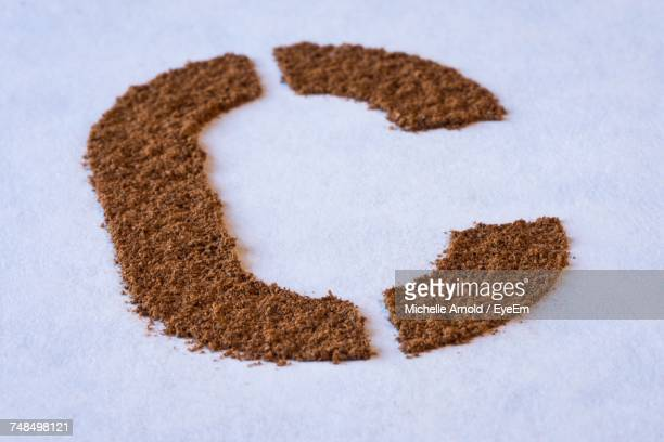 High Angle View Of Letter C Made From Ground Cinnamon On White Table