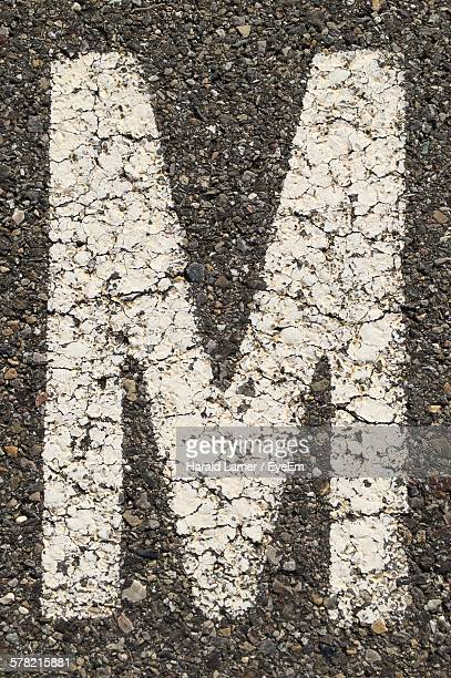 High Angle View Of Letter M On Road