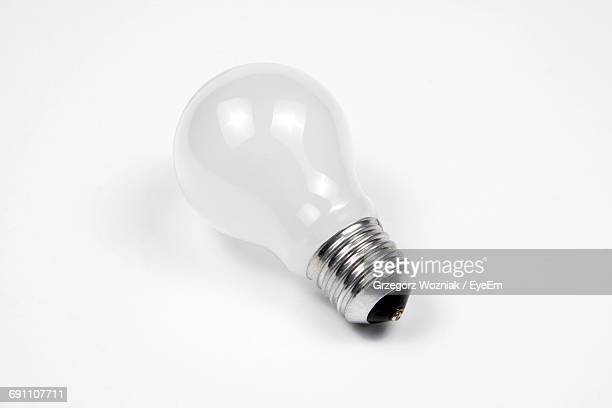 high angle view of light bulb on white background - light bulb stock photos and pictures