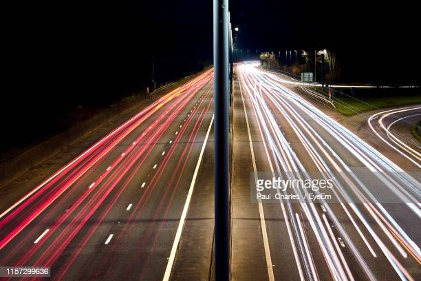 high angle view of light trails on highway at night - motorway stock pictures, royalty-free photos & images