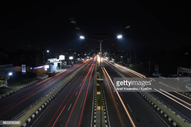 high angle view of light trails on highway at night - makassar stock pictures, royalty-free photos & images