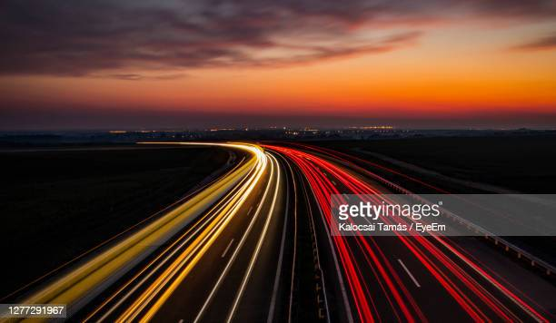 high angle view of light trails on highway at sunset - speed stock pictures, royalty-free photos & images