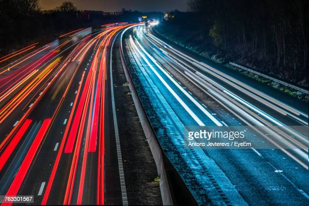high angle view of light trails on road at night - streak stock photos and pictures