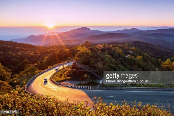 high angle view of light trails on road by mountains - mountain road stock pictures, royalty-free photos & images