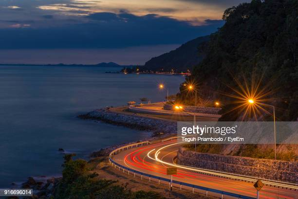 high angle view of light trails on road by sea against sky - chanthaburi sea stock pictures, royalty-free photos & images
