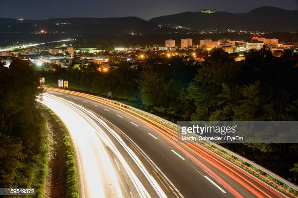 high angle view of light trails on road in city - sankt poelten stock pictures, royalty-free photos & images