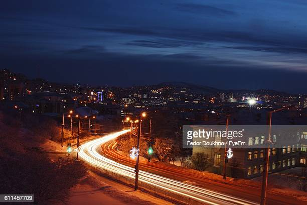 high angle view of light trails on street by buildings at night - fedor stock pictures, royalty-free photos & images