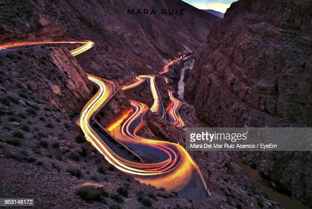 High Angle View Of Light Trails On Winding Road Amidst Mountains