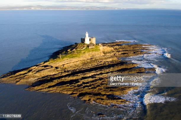 High Angle View Of Lighthouse Amidst Sea And Buildings