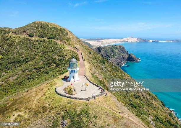 high angle view of lighthouse on mountain by sea against sky - whangarei heads stock-fotos und bilder