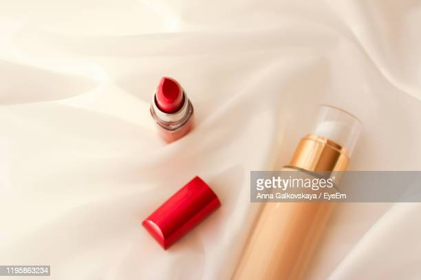high angle view of lipstick and liquid foundation bottle on satin - concealer stock pictures, royalty-free photos & images