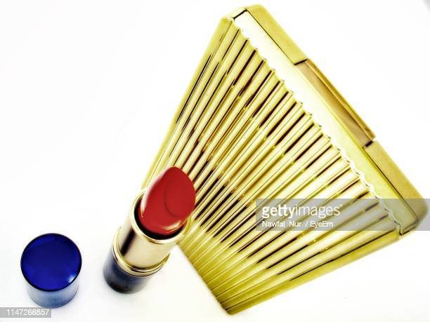 High Angle View Of Lipstick And Purse Against White Background