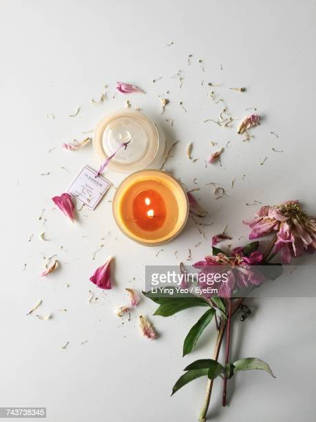 High Angle View Of Lit Candle With Wilted Flowers On White Table