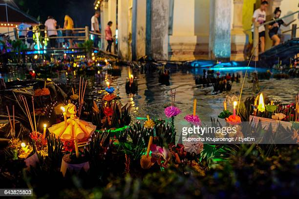 high angle view of lit candles and decoration by river during loi krathong - loi krathong stock photos and pictures