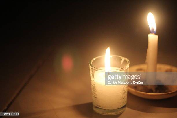 High Angle View Of Lit Candles On Table In Darkroom