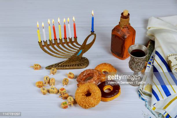 high angle view of lit colorful candles with food and drink on wooden table - hanukkah stockfoto's en -beelden