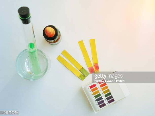 high angle view of litmus test papers and alkaline against white background - ph value stock pictures, royalty-free photos & images